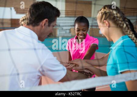 Entraîneur et joueurs de basket-ball avec leurs mains empilées en cour Banque D'Images