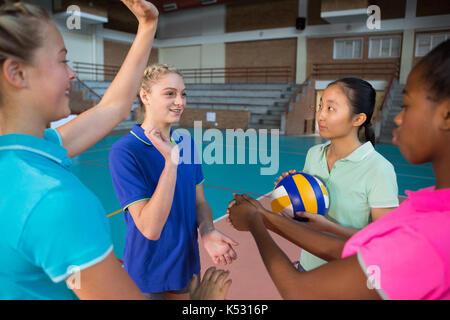 Les joueurs de volley-ball avec leurs mains empilées en cour Banque D'Images
