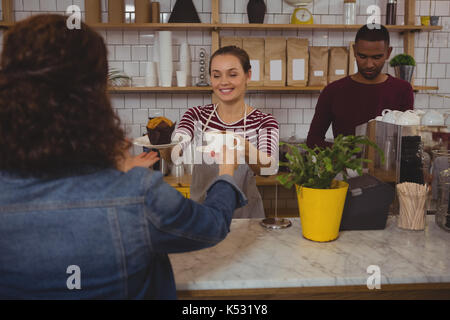 Jeune femme propriétaire servant du café et un muffin au client au café Banque D'Images