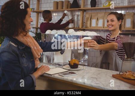 Jeune femme propriétaire pour servir le café au café client Banque D'Images