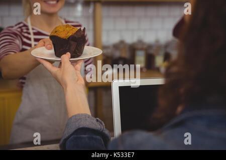Section intermédiaire de femme propriétaire servant à muffin au cafe client Banque D'Images