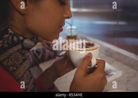 Close-up of young woman having coffee in cafe