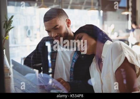 Young woman leaning on vu à travers l'épaule de l'homme en verre cafe