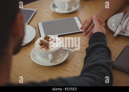 Portrait de couple holding hands par tasse de café à la table in cafe Banque D'Images