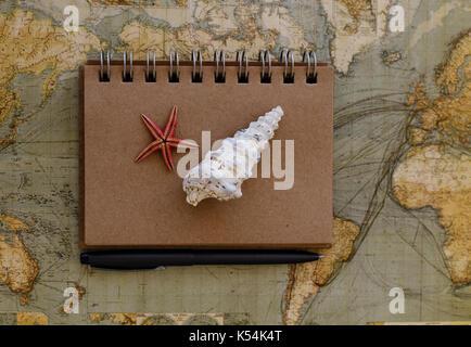 Télévision voyage jeter avec le bloc-notes les coquillages seastar et stylo noir placé sur la carte du monde Banque D'Images