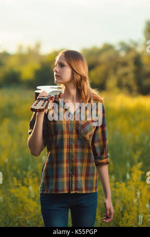 ... Belle jeune fille en jeans et chemise à carreaux avec guitare sur  l épaule 265aa81c8d2