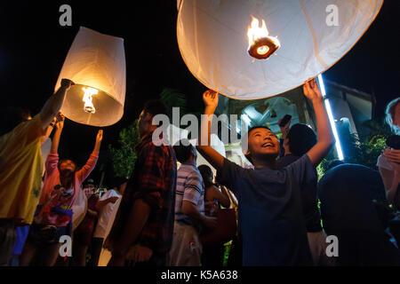 Chiang Mai, Thaïlande - 30/12/2015: un garçon libère une lanterne flottante dans un temple pour le nouvel an à Banque D'Images
