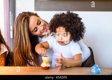 Une jeune mère assise à la table de cuisine avec son petit enfant afro dans sa tour Banque D'Images