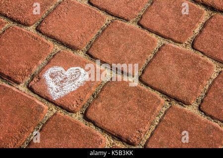 Dessin à la craie d'un cœur sur la brique sett fond des chaussées Banque D'Images