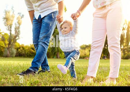 Les premiers pas du bébé. Une famille heureuse. Banque D'Images