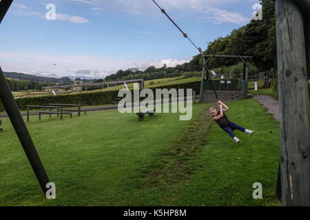 Girl having fun on zip wire adventure play park dans la région de Denny, Ecosse Banque D'Images