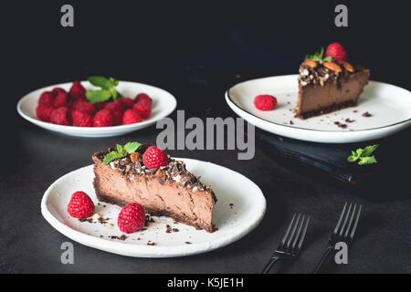 Deux morceaux de gâteau au fromage au chocolat décoré avec des framboises et de la menthe sur fond sombre. Composition Banque D'Images
