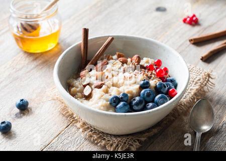 Gruau d'avoine avec des bleuets, amandes, cannelle, miel, linseeds et groseilles rouges dans un bol. super aliment Banque D'Images