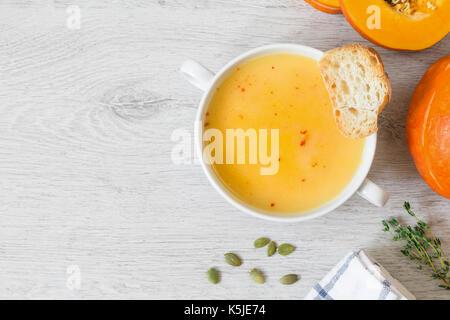 Crème de potiron soupe avec les flocons de poivron rouge et de pain grillé dans un bol sur fond gris. Vue de dessus Banque D'Images