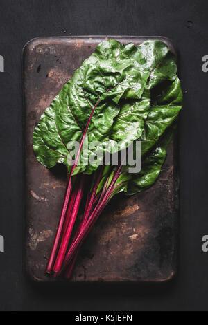Feuilles de bette à carde fraîche sur fond sombre rusty. Vue de dessus de table produits frais bio green food Banque D'Images