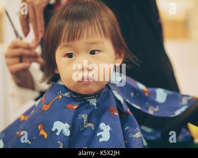 Asian baby girl faire couper les cheveux première fois dans la coiffure shop Banque D'Images