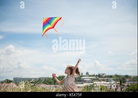 Heureux petite fille aux longs cheveux holding flying kite dans le domaine de l'été journée ensoleillée Banque D'Images
