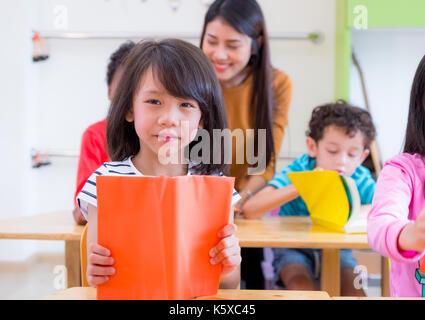 Asian girl kid reading book en classe et tout en enseignant enseigner les amis à côté d'eux, l'école maternelle l'éducation préscolaire.