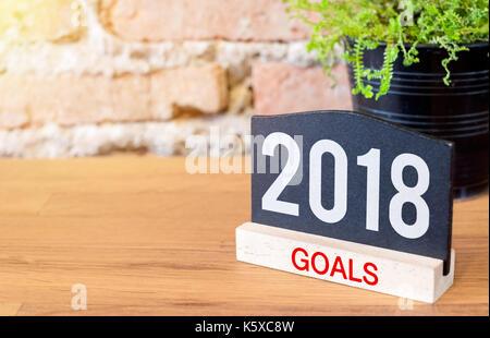 Nouvelle année 2018 buts sur tableau noir signe et plante verte sur la table en bois au mur de brique Banque D'Images
