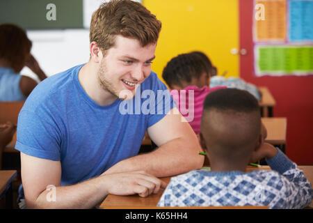 Enseignant bénévole masculin blanc garçon aidant à l'école élémentaire class Banque D'Images