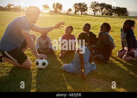 Les enfants de l'école élémentaire et des enseignants assis avec ball in field Banque D'Images