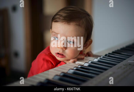 Curieux boy leaning on piano Banque D'Images
