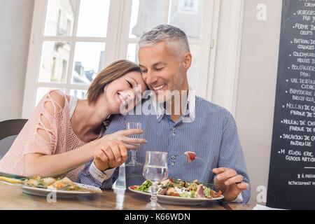 Caucasian couple cuddling in restaurant Banque D'Images