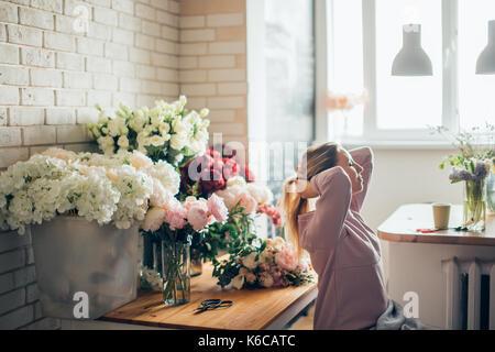 Heureux belle jeune femme fleuriste à lunettes assis dans le magasin de fleurs Banque D'Images
