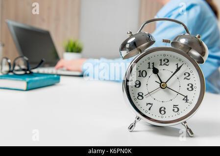 In l'office, dans l'accent, d'un réveil sur une table close-up Banque D'Images