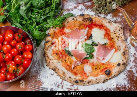 Pizza italienne traditionnelle à base de tomates, mozzarella, jambon et les ingrédients sur la table en bois Banque D'Images