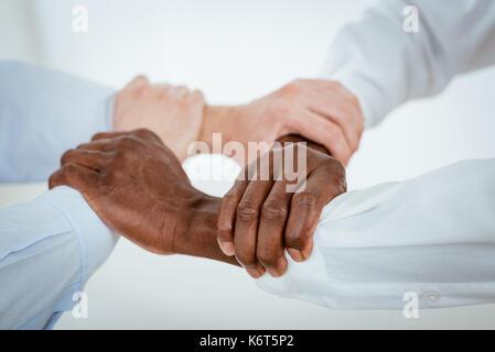 Close-up d'un noir et blanc quatre mains tenant ensemble hermétiquement. Banque D'Images
