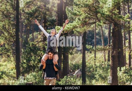 Randonnées couple tout en trekking dans la forêt. Woman riding piggyback sur l'homme avec les bras tendus au cours Banque D'Images