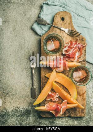 Vin d'été. flatlay partie fixe de vin snack-jambon prosciutto, melon et verres de vin rose avec de la glace sur Banque D'Images