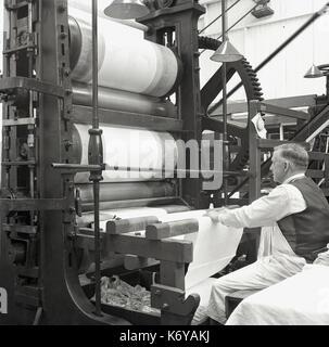 Années 1950, un homme travailleur du textile à l'aide d'appareils mécaniques, rouleaux, pour nettoyer et lisser Banque D'Images