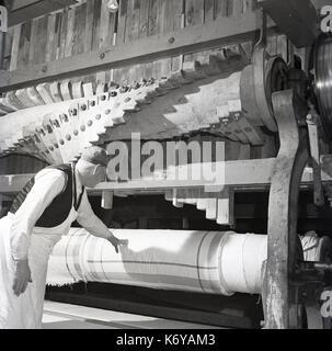 Années 1950, l'Irlande du Nord, homme travailleur du textile contrôle de la qualité du tissu en lin fermement enroulés Banque D'Images