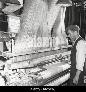 Années 1950, l'Irlande du Nord, un homme travailleur du textile dans un gilet et cap à l'aide d'un métier mécanisé Banque D'Images