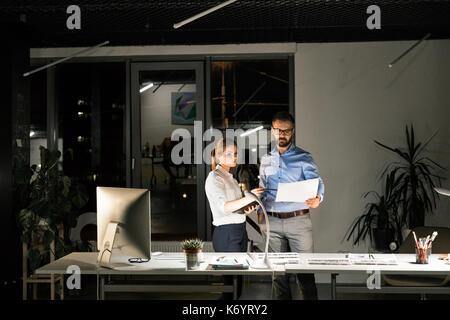 Deux jeunes gens d'affaires dans le bureau au travail tard la nuit, discuter d'un projet. Banque D'Images