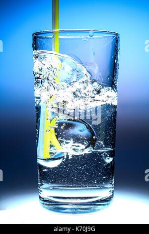 Rafraîchissant cool verre d'eau avec une paille et des bulles isolées sur un fond bleu Banque D'Images