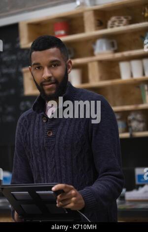 Portrait de propriétaire à l'aide d'ordinateur tout en se tenant au comptoir de cafe Banque D'Images