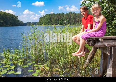 Adolescent garçon et fille d'âge élémentaire assis sur une jetée en bois d'une forêt d'été profiter du lac journée Banque D'Images
