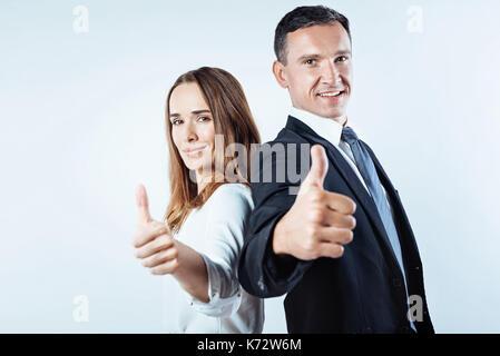 L'équipe d'affaires posant avec un geste super Banque D'Images