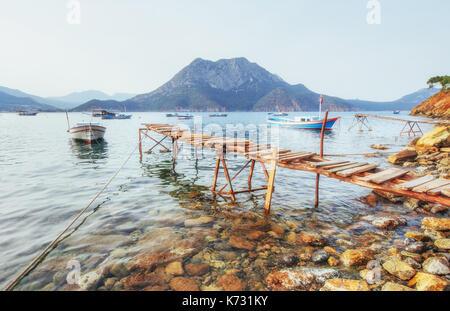 Bateaux près de la jetée de cassé, la mise dans un calme paisible de l'eau de mer bleue Banque D'Images