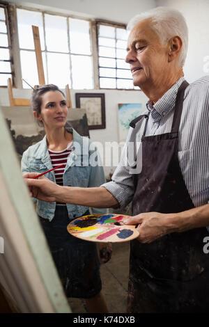 Alors que l'interaction femme senior man painting on canvas en classe de dessin Banque D'Images