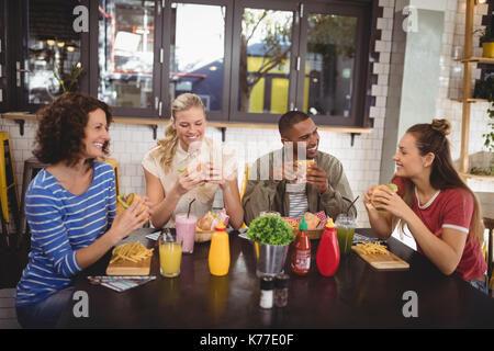 Smiling young friends eating food while sitting at table in coffee shop Banque D'Images