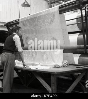 Années 1950, historiques, l'homme contrôle l'impression des rouleaux de lin irlandais, l'Irlande du Nord. Banque D'Images