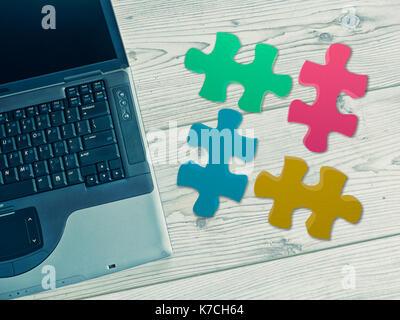 Vue du dessus de l'ordinateur portable sur une table en bois avec des puzzles Banque D'Images