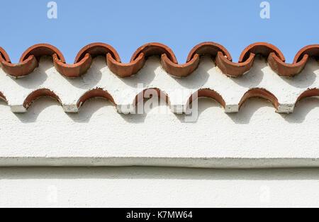 Des toits de tuiles rouges et mur blanc contre ciel bleu Banque D'Images