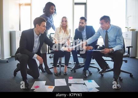 Groupe diversifié de businesspeople sitting et de planification avec la paperasse disposés sur le plancher tout Banque D'Images