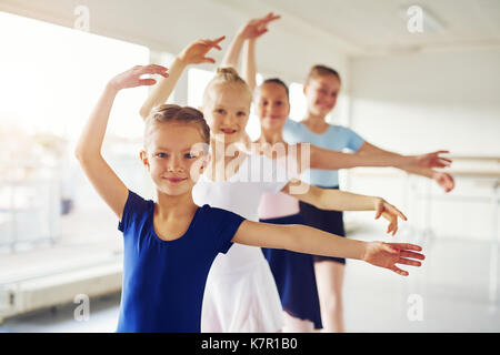 Peu de jeunes filles gaies performing ballet et smiling at camera dans la classe. Banque D'Images