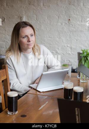 Young businesswoman sitting at table en bois à barres ayant un comprimé sur 24 amis d'écoute Banque D'Images